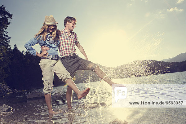 Germany  Bavaria  Couple playing in water  smiling