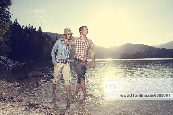 Deutschland  Bayern  Paar im Wasser laufen  lächelnd