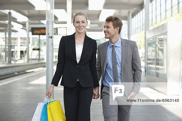 Germany  North Rhine Westphalia  Duesseldorf  Couple with shopping bags in station  smiling