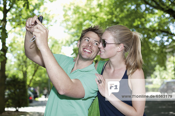 Germany  North Rhine Westphalia  Duesseldorf  Couple taking photo of themselves  smiling