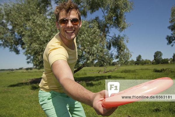 Germany  North Rhine Westphalia  Duesseldorf  Mid adult man playing with frisbee  smiling