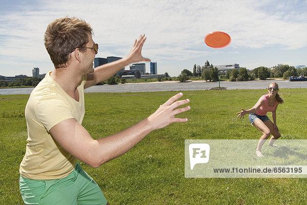 Germany  North Rhine Westphalia  Duesseldorf  Couple playing with frisbee