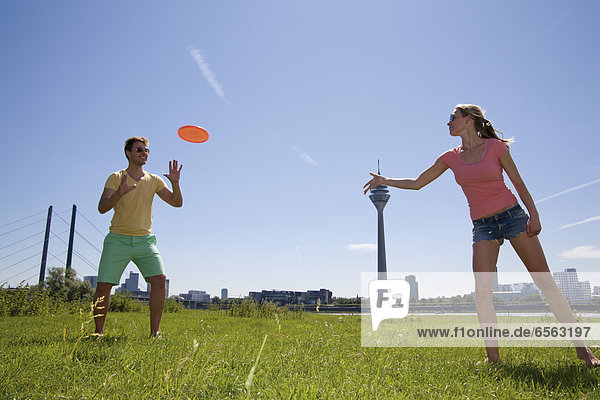 Germany  North Rhine Westphalia  Duesseldorf  Couple playing with frisbee