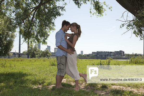 Germany  North Rhine Westphalia  Duesseldorf  Couple embracing on grass  smiling