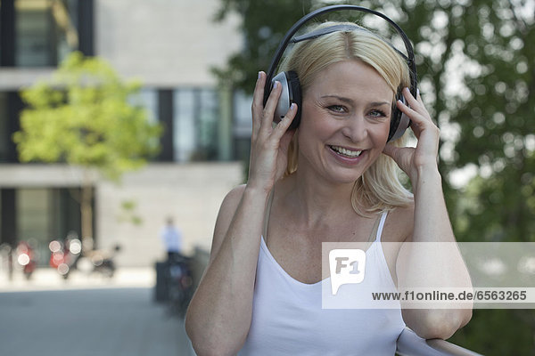 Mid adult woman with headphone  smiling