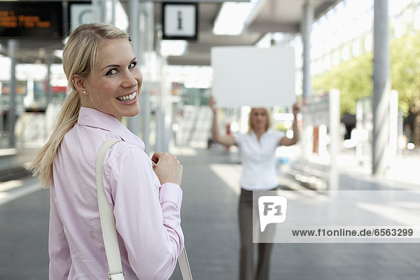 Young businesswoman smiling  another woman holding placard in background