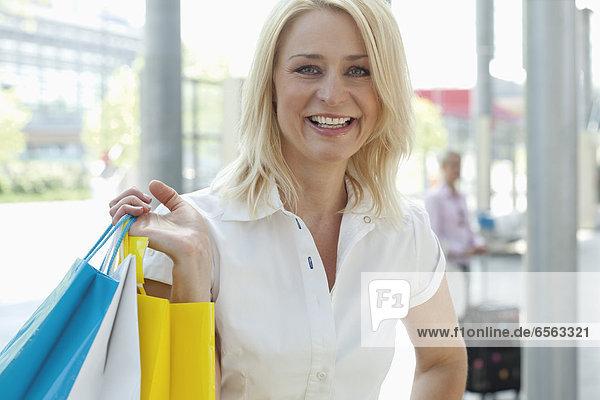 Geschäftsfrau mit Einkaufstasche  eine weitere Frau mit Trolley im Hintergrund
