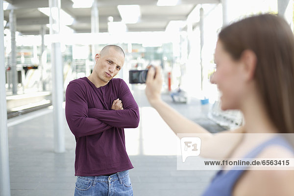 Young woman taking photograph of man