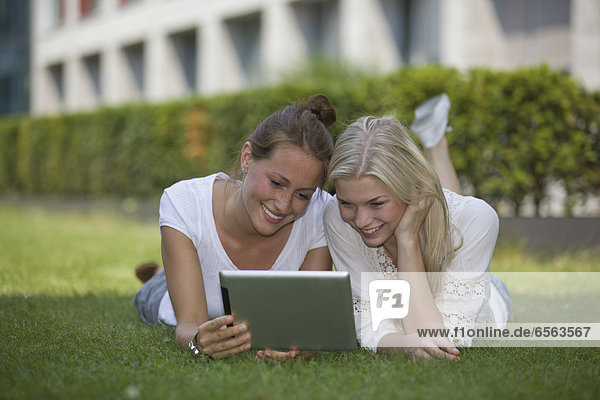 Germany  North Rhine Westphalia  Cologne  Young students with digital tablet  smiling
