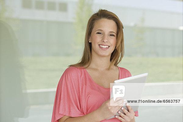Europa  Deutschland  Nordrhein-Westfalen  Düsseldorf  Junge Frau mit digitalem Tablett  lächelnd  Portrait