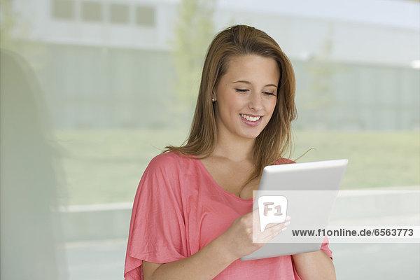 Europa  Deutschland  Nordrhein-Westfalen  Düsseldorf  Junge Frau mit digitalem Tablett  lachend