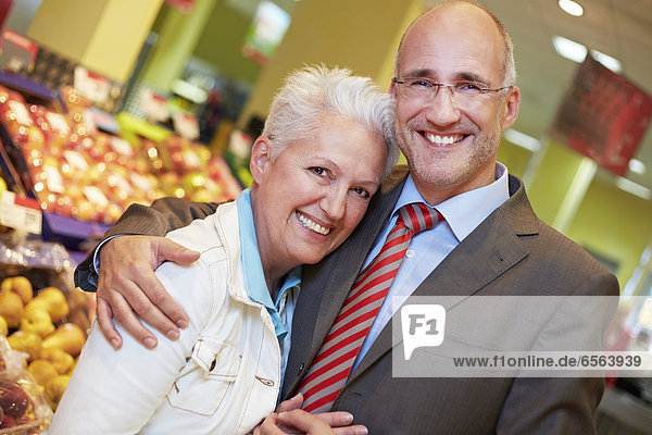 Germany  Cologne  Mature couple in supermarket  smiling  portrait
