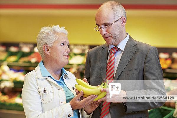 Deutschland  Köln  reifes Paar mit Bananen im Supermarkt