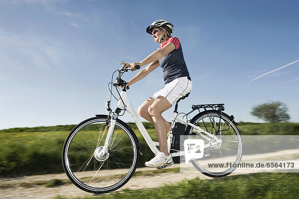 Mature woman riding electric bicycle