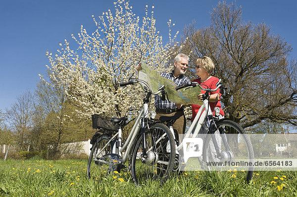 Deutschland  Bayern  Seniorenpaar beim Beobachten der Straßenkarte