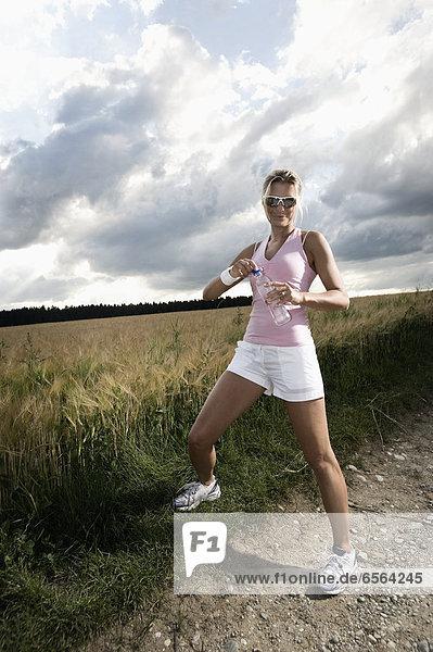 Reife Frau mit Wasserflasche im Getreidefeld