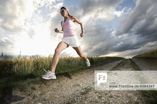 Reife Frau  die im Getreidefeld läuft