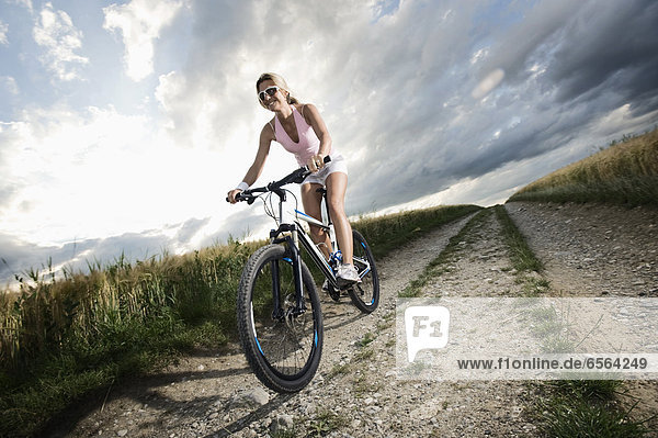 Reife Frau auf dem Mountainbike im Getreidefeld