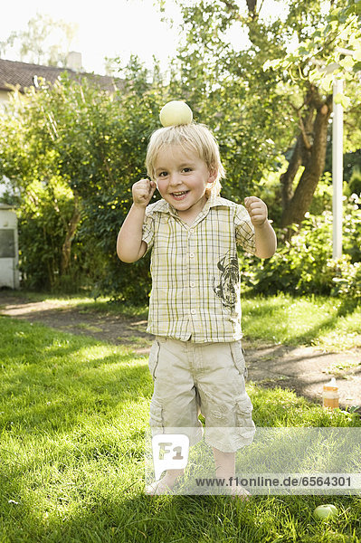 Boy playing with apple on top of head