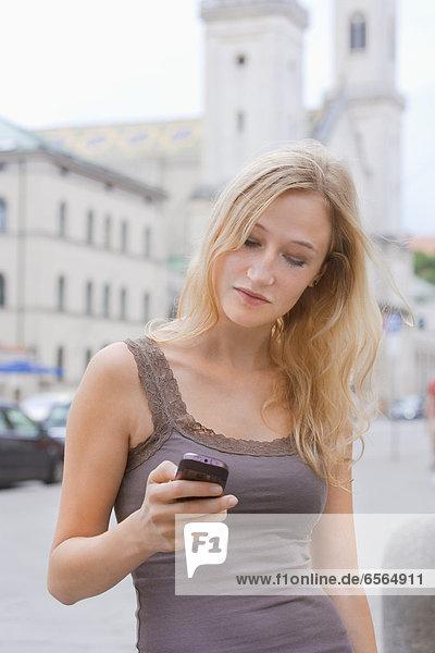Junge Frau mit Smartphone vor der Ludwig-Maximilians-Universität