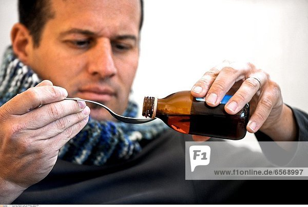 Man taking a cold syrup *** Local Caption ***