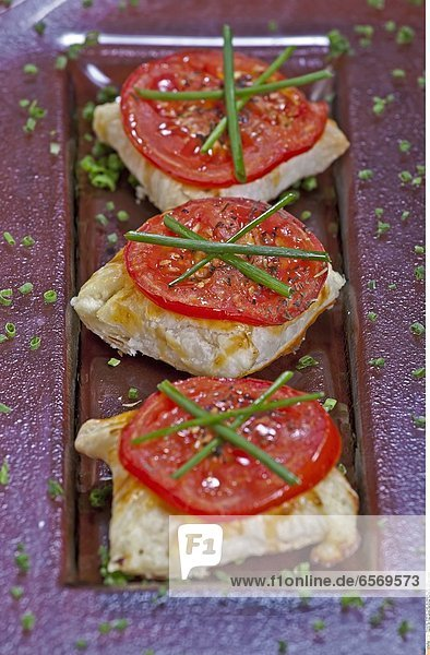 Mit KŠse gefŸllte BlŠtterteig-Taschen mit gegrillter Tomate