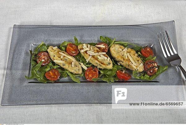 Quark-Rucola-KŠsschen auf einem Rucola-Bett mit gebratenen Tomaten