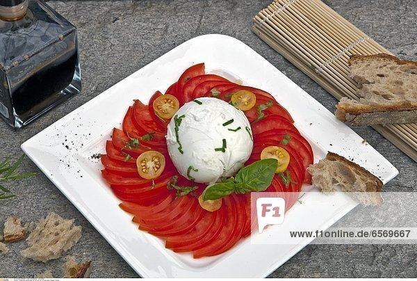 Tomate-Mozzarella-Salat  serviert auf der Terrasse eines Tessiner Grottos