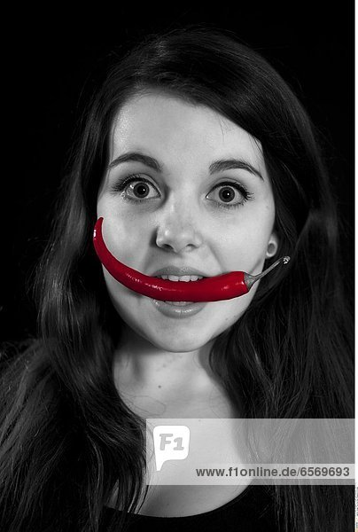 Junge Frau mit einer Pepperoni im Mund