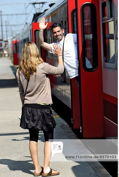 Young couple traveling by train. Goodbyes on a station platform *** Local Caption ***