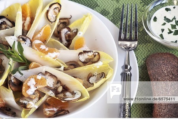 Chicoree-Salat mit Mandarinen  Champignons und Pinienkernen
