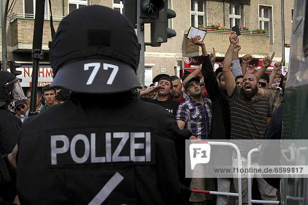 Protest against an anti-Islamic rally by the minor political party Pro Deutschland in front of a mosque in Berlin-Neukoelln  agitated demonstrators holding copies of the Koran in the air  Berlin  Germany  Europe