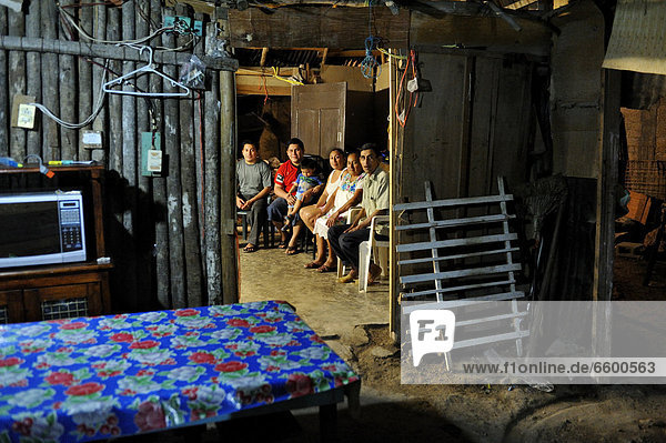 Family of a couple that works in the tourism industry  people sitting in a humble wooden hut at night  on the outskirts of Cancun  Yucatan Peninsula  Quintana Roo  Mexico  Latin America  North America