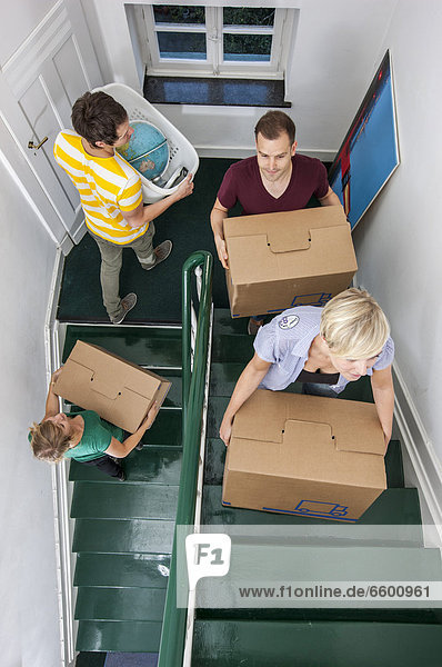 Private house move  friends helping  carrying boxes up the stairs