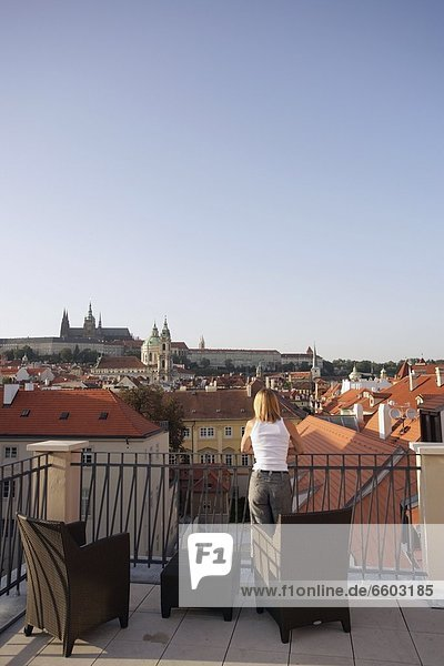 Woman Leaning On Roof Terrace Looking Over Prague Cityscape