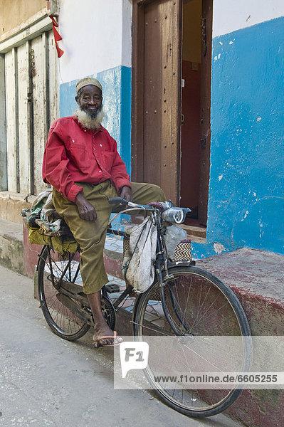 Mann auf einem Fahrrad in Stone Town  Sansibar  Tansania  Afrika