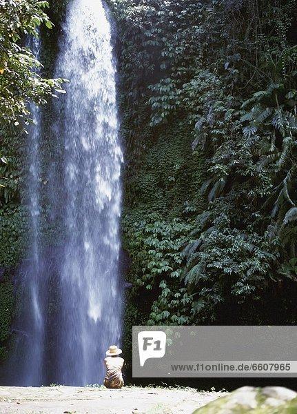 Woman Sitting Beside Waterfall  Sendang Gila