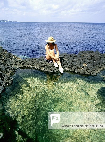 Woman Sitting By Rock Pools With Sea Behind
