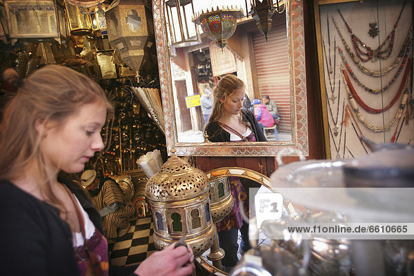 Young Woman Browsing For Antiques In A Market Stall In The Souk.