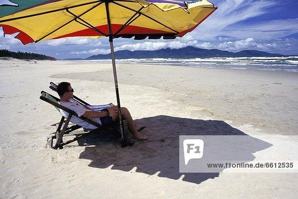 sitzend  Mann  Strand  Regenschirm  Schirm  unterhalb  Liege  Liegen  Liegestuhl  Seitenansicht  Sonnenschirm  Schirm