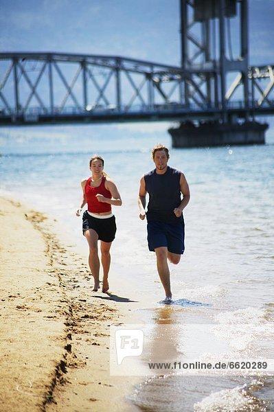 Wasserrand Zusammenhalt joggen vorwärts