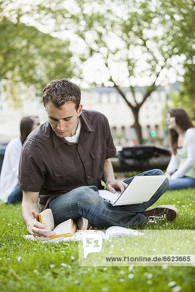Caucasian man studying in grass