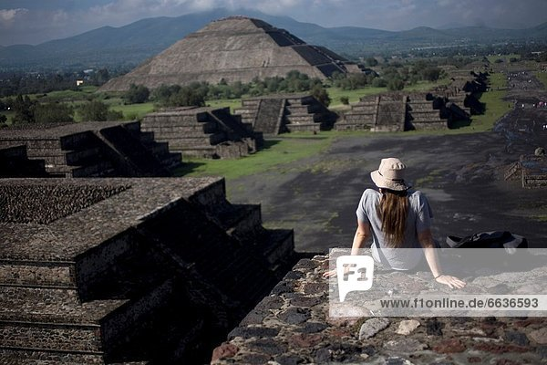 """A woman looks at the Pyramid of the Sun  back left  from the Pyramid of the Moon in Teotihuacan  Mexico City Teotihuacan that means """"City of the Gods´ and was founded by the Teotihuacanos around 500 BC and reach its peak some time around 500 AD A legend s. A woman looks at the Pyramid of the Sun  back left  from the Pyramid of the Moon in Teotihuacan  Mexico City Teotihuacan that means """"City of the Gods´ and was founded by the Teotihuacanos around 500 BC and reach its peak some time around 500 AD A legend says that the city was built by a race of giants Even today  it remains a mystery as no written records were left and the builders´ culture had ended before the Spaniards arrived"""