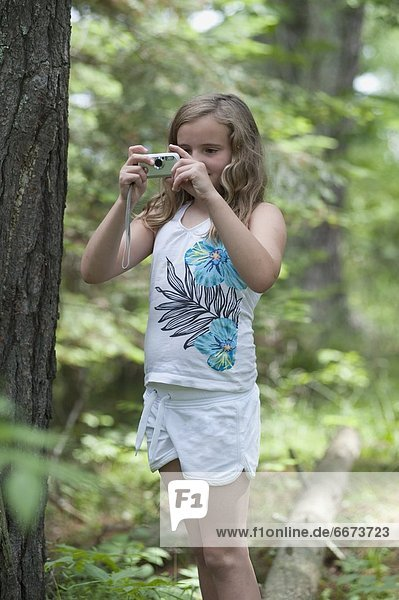 Girl Taking A Picture In A Forest