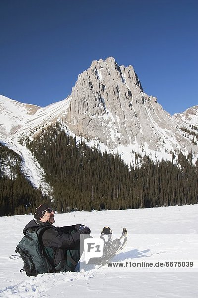 Man In Snowshoes Sitting In The Snow