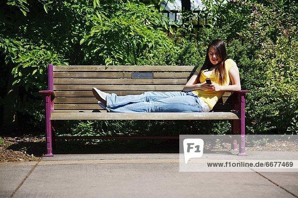 Handy  sitzend  benutzen  Jugendlicher  Sitzbank  Bank  Mädchen