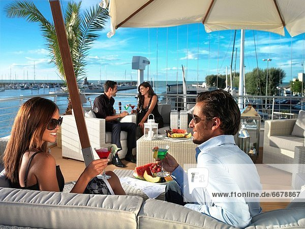 Couples having cocktail outdoors