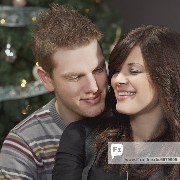 A Couple By The Christmas Tree