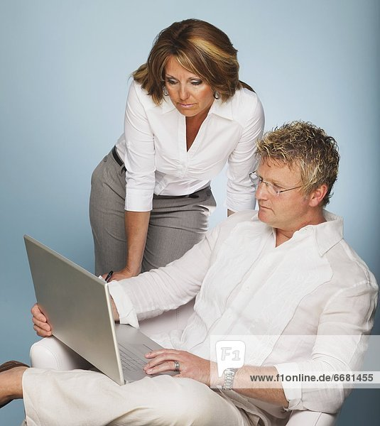 A Man And Woman Looking At A Laptop Computer