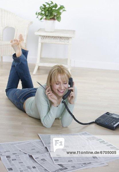 Frau sprechen Zeitung telefoniert